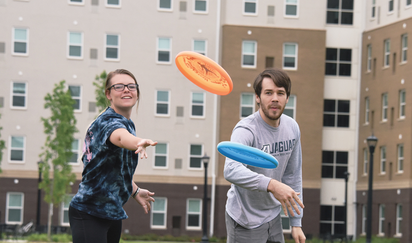 Jessica Fleming and James Crockett play Frisbee on the Jaguar Park greenspace.