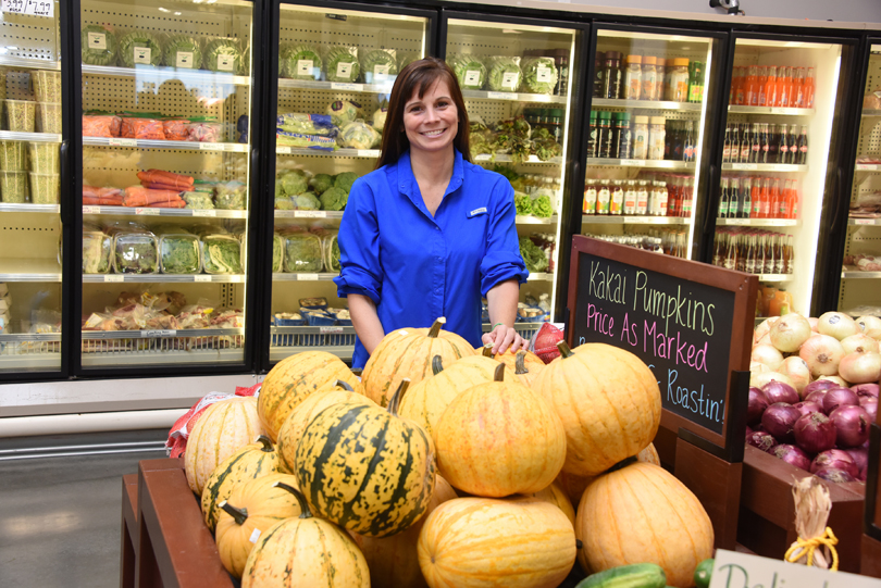 Dr. Maleah Holland poses with ketogenic diet-friendly foods at Good Earth Produce & Garden Center.