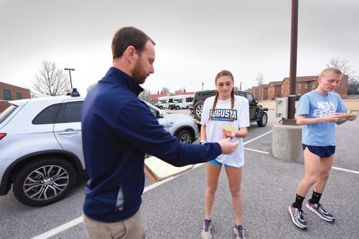 Coach Adam West hands out assignments.