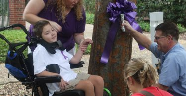 Epilepsy patient Preston Weaver gets help from his mom and others to hang a purple ribbon during Epilepsy Awareness Month in 2015.