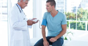 Doctor examining his patients blood pressure in medical office