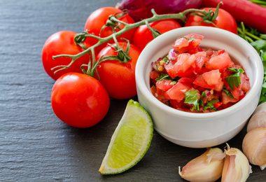 Salsa sauce and ingredients, dark stone background
