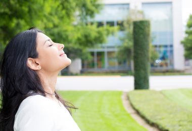 Closeup portrait young woman in white shirt breathing in fresh crisp air after long day of work isolated outdoors outside background. Stop and smell the roses connect with nature