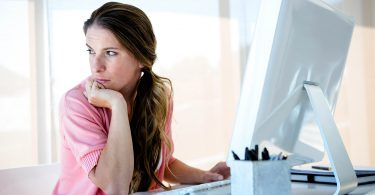 distracted business woman sitting at her desk, looking away from