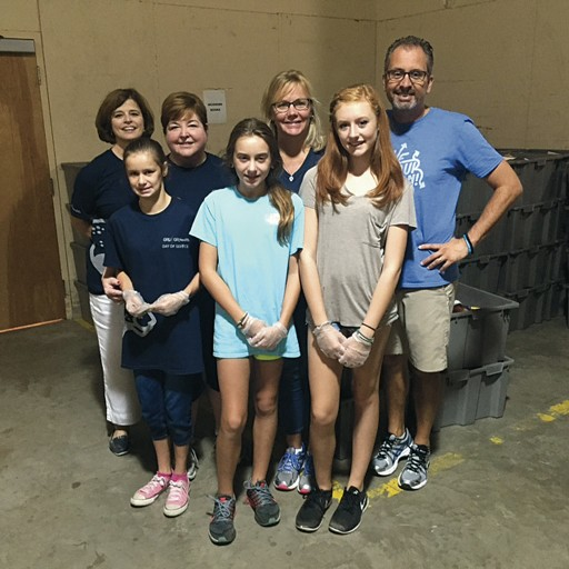 Dean Lefebvre and daughter Caitlin (second from left) sorted books at Goodwill's Good Books Cafe with Betty Meehan of the Office of Advancement (left) and Drs. Scott De Rossi and Kate Ciarrocca and their daughters, Sofia and Evie.